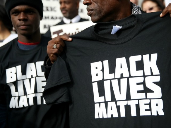 """SAN FRANCISCO, CA - DECEMBER 18:  A protestor holds a black lives matter t-shirt during a """"Hands Up, Don't Shoot"""" demonstration in front of the San Francisco Hall of Justice on December 18, 2014 in San Francisco, California. Dozens of San Francisco public attorneys and activists staged a """"Hands Up, Don't Shoot"""" demonstration to protest the racial disparities in the criminal justice system following the non-indictments of two white police officers who killed unarmed black men in Missouri and New York.  (Photo by Justin Sullivan/Getty Images)"""