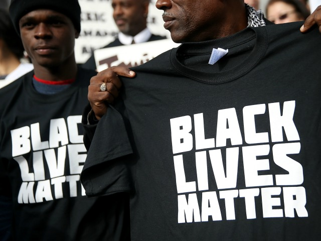 "SAN FRANCISCO, CA - DECEMBER 18:  A protestor holds a black lives matter t-shirt during a ""Hands Up, Don't Shoot"" demonstration in front of the San Francisco Hall of Justice on December 18, 2014 in San Francisco, California. Dozens of San Francisco public attorneys and activists staged a ""Hands Up, Don't Shoot"" demonstration to protest the racial disparities in the criminal justice system following the non-indictments of two white police officers who killed unarmed black men in Missouri and New York.  (Photo by Justin Sullivan/Getty Images)"