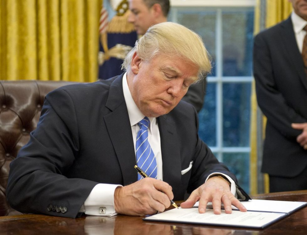 """WASHINGTON, DC - JANUARY 23:  (AFP OUT) U.S. President Donald Trump signs the last of three Executive Orders in the Oval Office of the White House in Washington, DC on Monday, January 23, 2017.  These concerned the withdrawal of the United States from the Trans-Pacific Partnership (TPP), a US Government hiring freeze for all departments but the military, and """"Mexico City"""" which bans federal funding of abortions overseas. (Photo by Ron Sachs - Pool/Getty Images) 694681111"""