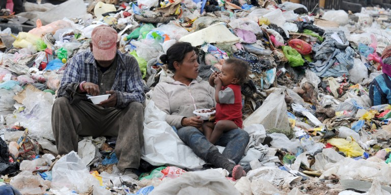 TO GO WITH AFP STORY BY MARIA ISABEL SANCHEZ A couple and their child have breakfast amid the garbage at the municipal rubbish dump, 20 km north of Tegucigalpa, on November 21, 2013.  Honduras, one of the poorest Latin American countries, will elect new president on November 24.  AFP PHOTO / Orlando SIERRA.        (Photo credit should read ORLANDO SIERRA/AFP/Getty Images)